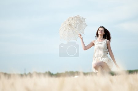 Photo for Beautiful sad and lonely woman with umbrella run in wheat field. Timed. - Royalty Free Image