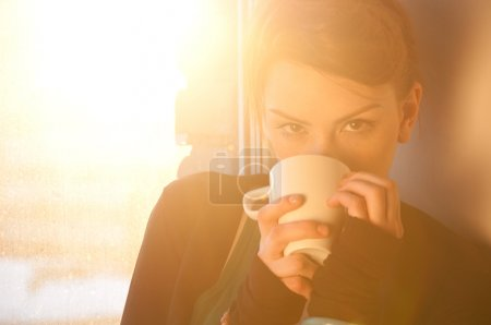 Photo for Beautiful young woman in casual wear dreaming with cup of hot coffee over window. Sun beam. - Royalty Free Image