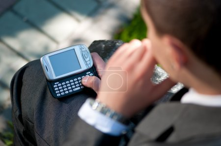 Photo for Young business man talking by mobile cell phone, at green park. Student. - Royalty Free Image