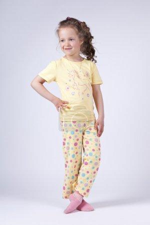 Photo pour Mignonne petite fille en jaune pajamasposing en studio - image libre de droit
