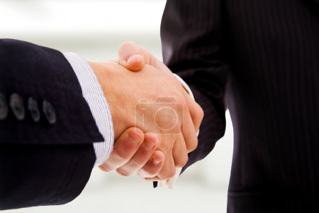 Closeup of business shaking hands at the office