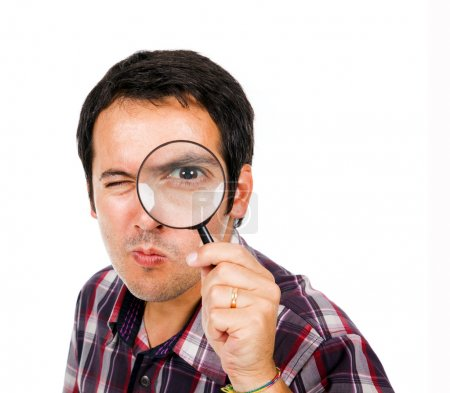 Funny young man looking through magnifying glass, isolated on wh