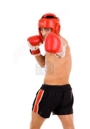 Photo pour Chasse de jeune boxeur avec casque de boxe et des gants, faire un coup de poing sur fond blanc - image libre de droit