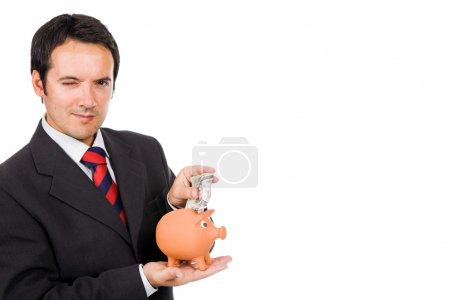 Business man inserting money into a piggy moneybox, isolated on
