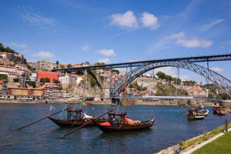 Tradicional vintage port transporting boats near famous bridge P