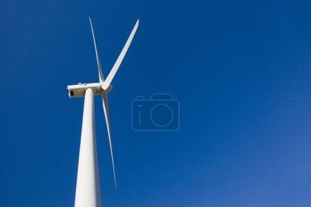 White wind turbine against blue sky