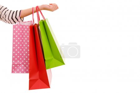 Female hand holding colorful shopping bags, isolated over white