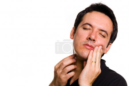 Close-up of young man in agony with toothache