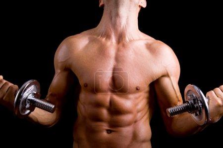 Muscular young man lifting dumbbells