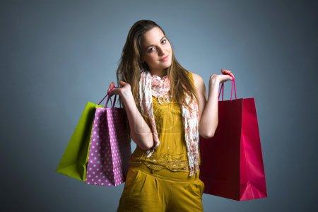 Photo pour Femme tenant des sacs à provisions sur un fond gris - image libre de droit