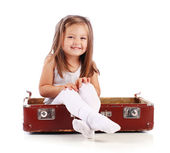 Happy small child sitting in a suitcase. Travel. Isolated on whi