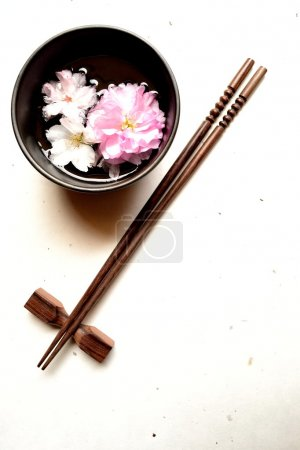 Small bowl of cherry blossom and chop sticks