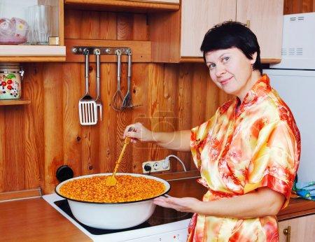 Photo pour Femme cuisine une confiture d'argousier - image libre de droit