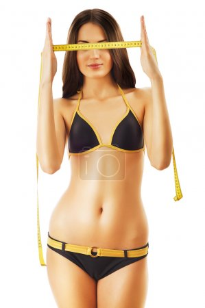 Slimming woman in swimsuit with measure on eyes
