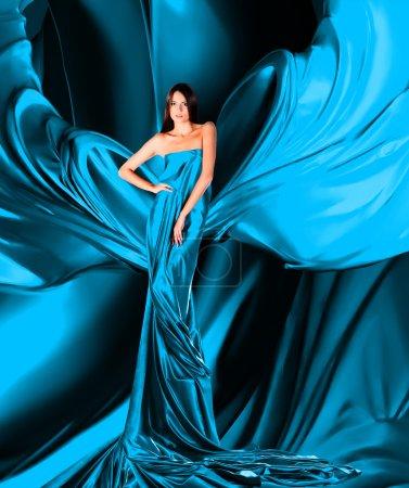 Photo pour Femme en robe longue bleue sur tissu rouge - image libre de droit