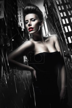 Sexy brunette woman with red lips in dark rainy city