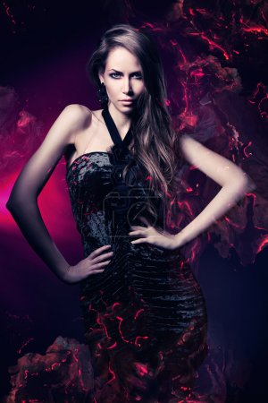 Sexy woman in black dress on dark magenta backgrou...