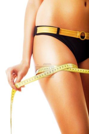 Slim woman with measure on leg