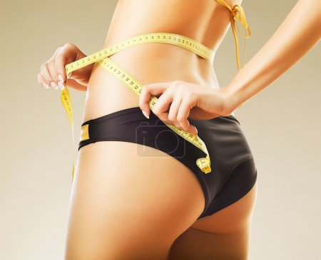 Photo for Slimming woman in panties with yellow measure - Royalty Free Image