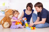 Happy parents playing with child at home