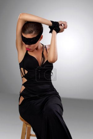 Attractive blindfolded girl sitting