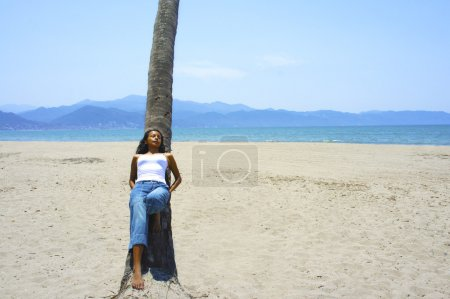 Photo for Young latina woman leaning on a palm tree. - Royalty Free Image