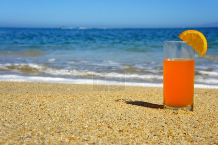 Photo for A glass of Orange Juice standing in the sand. - Royalty Free Image