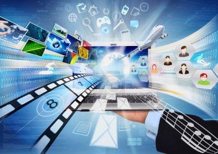 Photo pour Image conceptuelle sur comment un ordinateur portable ouvert connet à l'information dans le monde entier et partage multimédia. - image libre de droit