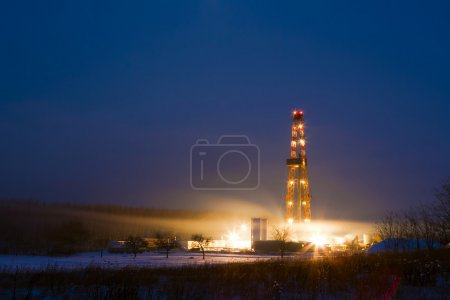 Ölbrunnen in der verschneiten Landschaft leuchtet in der Nacht.