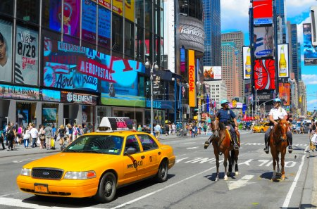 Photo for Police and taxi at a Times Square Intersection in New York, NY. It is the world's most visited tourist attraction bringing over 39 million annually. - Royalty Free Image