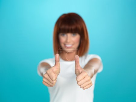 Attractive woman smiling with her thumbs up