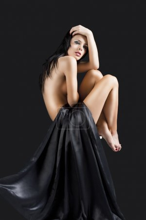 The nude cute sexy woman over black with hand on the head