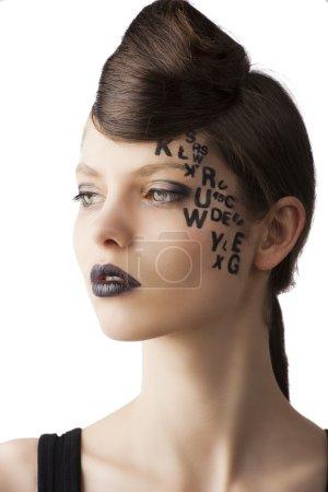 Photo pour Très jolie jeune fille avec la lettre et numéro peint sur son visage et une belle coiffure créative, elle est tournée de trois quarts à droite et regarde devant elle - image libre de droit