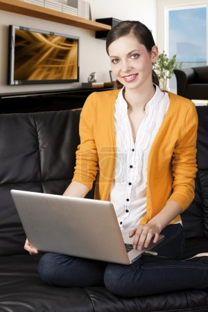 Girl on sofa with laptop, she smiles and looks in to the lens