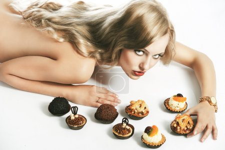 Blond sexy girl eating pastry, she looks in to the lens