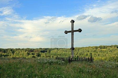 Photo pour Croix chrétienne en bois sur une colline couverte d'herbe (et une colonie forestière lointaine) ) - image libre de droit