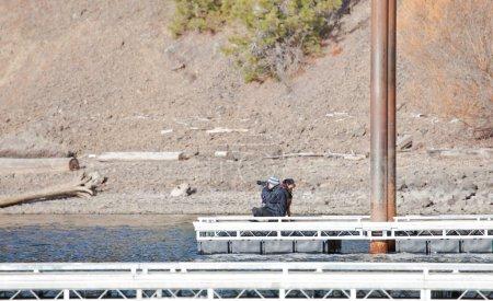 Photo pour Femme promener son chien sur un quai au bord du lac dans l'idaho - image libre de droit