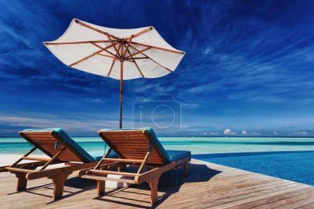 Deck chairs and infinity pool over tropical lagoon