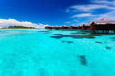 Overwater bungallows in blue tropical lagoon