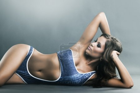 Portrait of a gorgeous lying woman in blue bikini