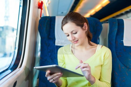 Mujer joven usando su tableta mientras viaja en tren