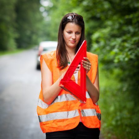Young female driver after her car has broken down