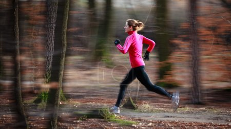 Photo for Young woman running outdoors in a city park on a cold fall/winter day (motion blurred image) - Royalty Free Image