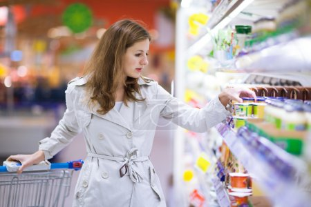 Beautiful young woman shopping in supermarket