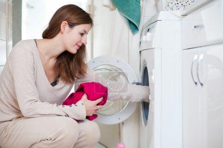 Photo pour Tâches ménagères: jeune femme en faisant la lessive (shallow dof; image couleur tonique) - image libre de droit