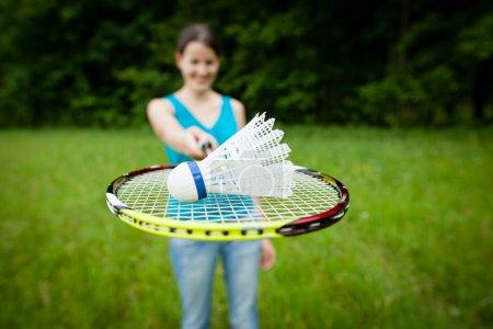 Photo pour Jolie, jeune femme jouant au badminton dans un parc de la ville par une belle journée d'été (peu profonde DOF ) - image libre de droit