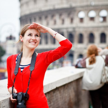 Photo for Portrait of a pretty young tourist taking photographs while sightseeing in Rome, Italy (with Colosseum in the background) - Royalty Free Image