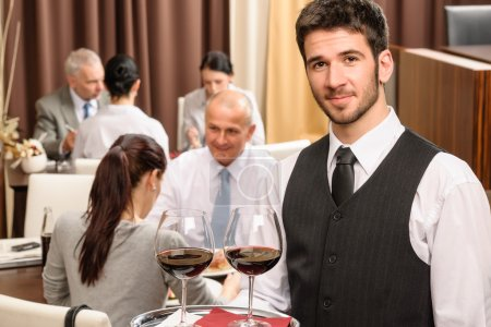 Photo for Young waiter hold red wine business lunch at professional restaurant - Royalty Free Image