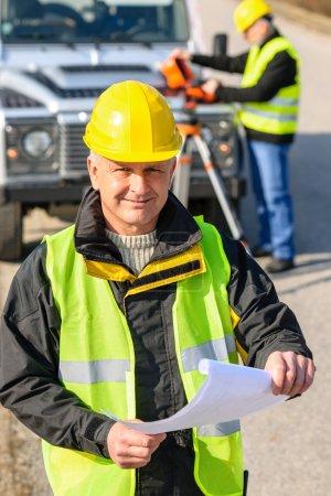 Land geodesist man hold plan reflective vest