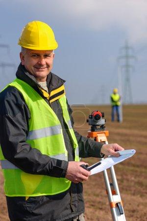 Geodesist measure land hold construction plans